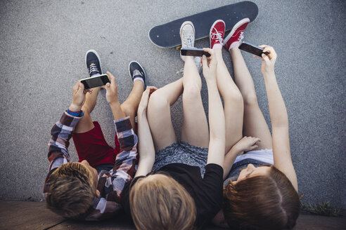 Three teenagers sitting outdoors with smartphones and skateboard - AIF000182