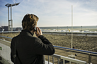 Germany, Frankfurt, Young businessman at the airport using smartphone - UUF006321