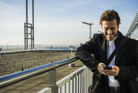 Germany, Frankfurt, Young businessman at the airport using smartphone - UUF006324