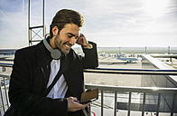 Germany, Frankfurt, Young businessman at the airport using smartphone with head phones - UUF006333
