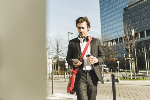 Germany, Frankfurt, Young businessman walking the city with cup of coffee, using mobile phone - UUF006345