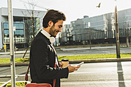 Germany, Frankfurt, Young businessman walking the city with cup of coffee, using mobile phone - UUF006348