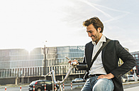 Germany, Frankfurt, Young businessman in the city with bicycle, using mobile phone - UUF006351