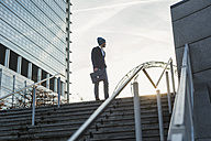 Germany, Frankfurt, Young businessman standing on stairs, looking away - UUF006357