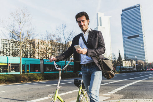 Germany, Frankfurt, Young businessman in the city with bicycle, using mobile phone - UUF006360