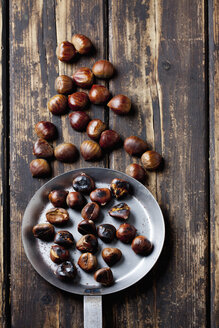 Fresh and roasted chestnuts on dark wood - CSF026963
