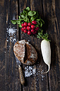 Crusty bread, bread knife, red radishes, radish and scattered salt grains on dark wood - CSF026972