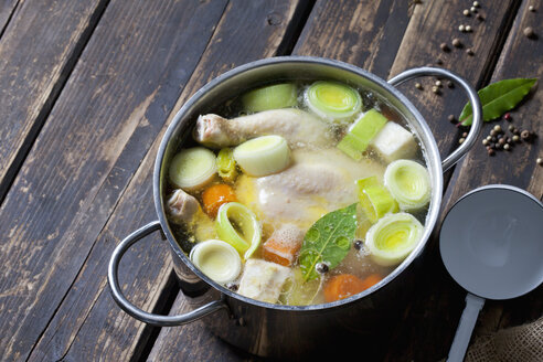 Cooking pot with raw corn-fed chicken, onion, herbs and greens - CSF026996
