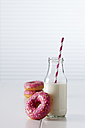 Glass bottle of milk and three doughnuts with pink icing on white ground - CSF026999