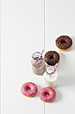 Two glass bottles of milk and cocoa and four doughnuts with different icings on white ground - CSF027005