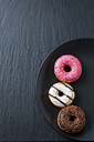 Three doughnuts with different icings on black plate and slate - CSF027014