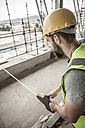 Construction worker using tape measure in construction site - ZEF007865