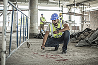 Construction worker spaying marks on floor in construction site - ZEF007883