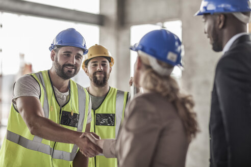 Construction worker and executive shaking hands in construction site - ZEF007895