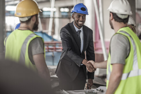 Construction worker and executive shaking hands in construction site - ZEF007898