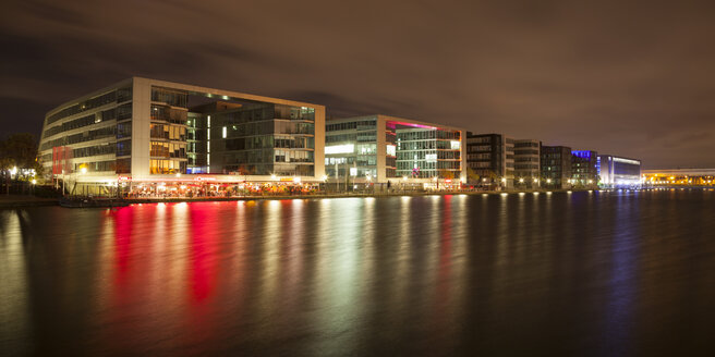 Germany, North Rhine-Westphalia, Duisburg, Inner harbour with office buildings and restaurants at night - WIF003083