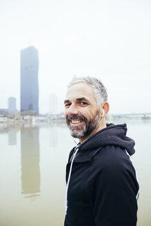 Austria, Vienna, portrait of smiling man with earphones on Danube Island - AIF000202