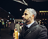 Austria, Vienna, man with Cheese Carniolan sausage at night - AIF000208