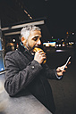 Austria, Vienna, man eating Cheese Carniolan sausage while looking at smartphone by night - AIF000211