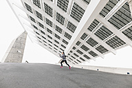 Spain, Barcelona, jogging woman under solar plant - EBSF001207