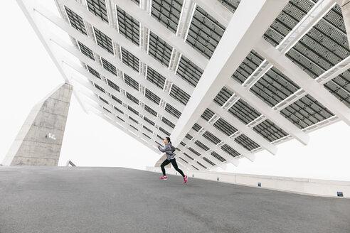 Spain, Barcelona, jogging woman under solar plant - EBSF001207
