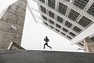 Spain, Barcelona, jogging woman under solar plant - EBSF001210