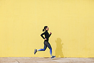 Spain, Barcelona, jogging woman in front of yellow wall - EBSF001222