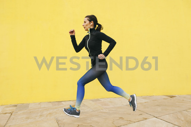 Spain, Barcelona, jogging woman in front of yellow wall - EBSF001225 - Bonninstudio/Westend61