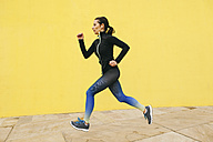 Spain, Barcelona, jogging woman in front of yellow wall - EBSF001225