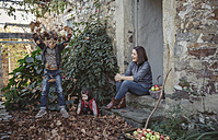 Spain, Asturias, woman sitting at entrance of country house watching her childs playing with autumn leaves - DAPF000003