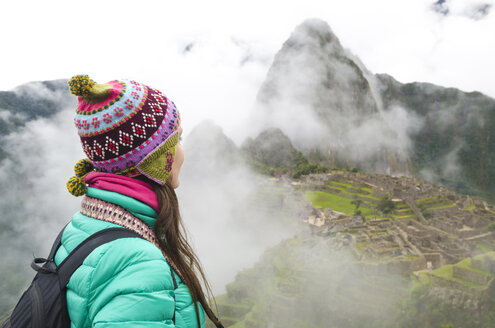 Peru, woman enjoying Machu Picchu before sunrise with the ruins surrounded by fog - GEMF000620