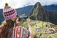 Peru, woman taking pictures of Machu Picchu citadel and Huayna Picchu mountain with a tablet - GEMF000626