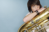 Portrait of teenage boy with tuba in front of blue background - GUFF000182