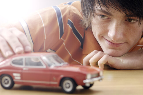 Portrait of smiling teenage boy with Ford Capri model car - GUFF000185