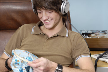 Portrait of smiling teenage boy with headphones and needlework - GUFF000188
