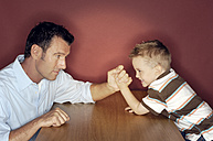 Little boy arm wrestling with his father - GUFF000191