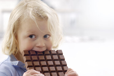 Portrait of little blond girl with chocolate bar - GUFF000209