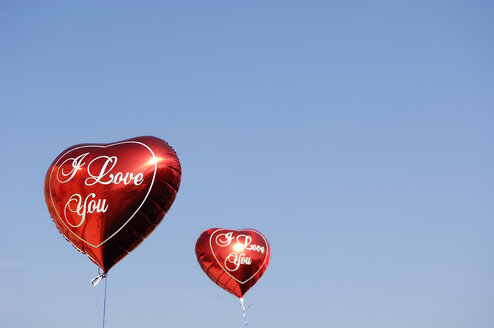 Two red heart-shaped balloons in front of blue sky - GUFF000215