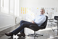 Confident businessman sitting in chair in office - RBF004006