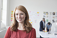 Portrait of smiling young woman in office - RBF004021