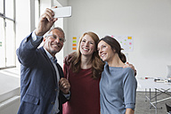 Smiling businessman taking a selfie with two women in office - RBF004024