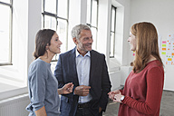 Smiling businessman and two women in office talking - RBF004027