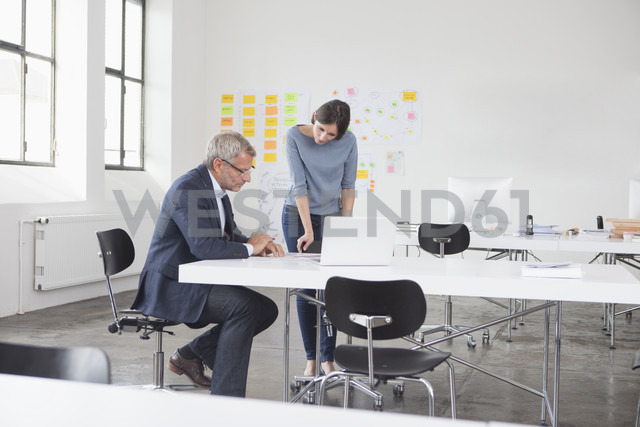 Businessman and two in office looking at laptop - RBF004033