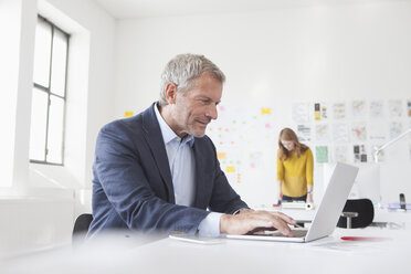 Smiling businessman in office at desk looking at laptop - RBF004045