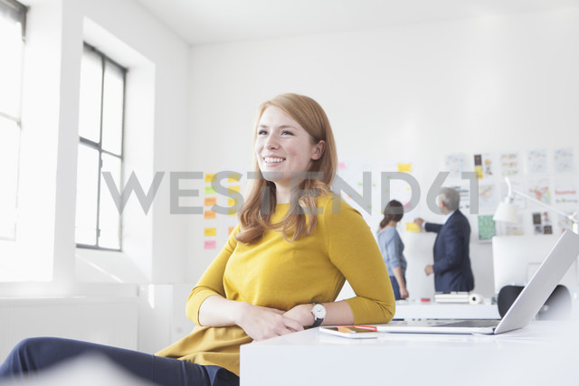 Smiling young woman in office at desk - RBF004048
