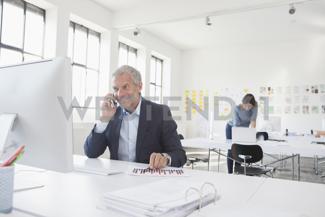 Smiling businessman in office at desk on cell phone - RBF004060
