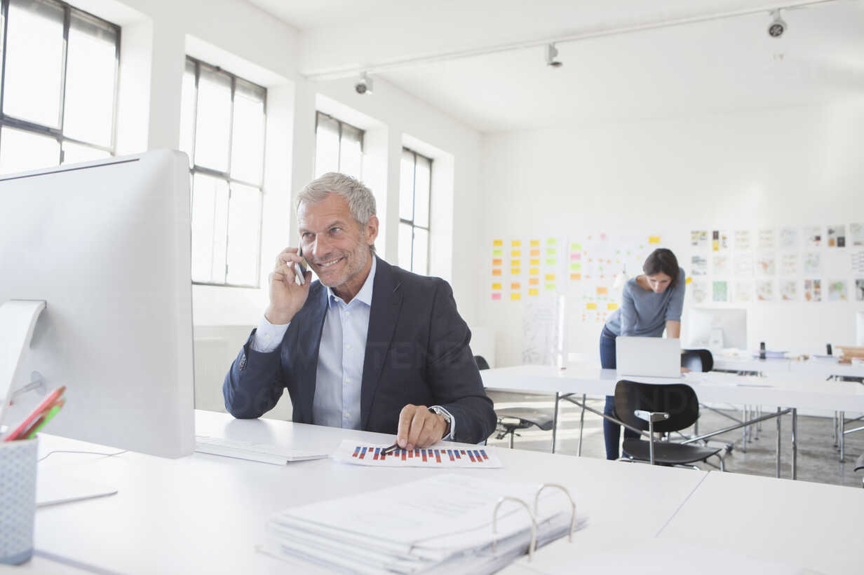 Smiling businessman in office at desk on cell phone - RBF004060 - Rainer Berg/Westend61