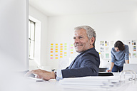 Smiling businessman in office at desk - RBF004063