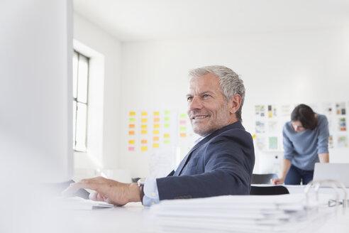 Smiling businessman in office at desk - RBF004063