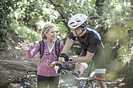 Man on mountainbike in forest talking to woman - ZEF007903